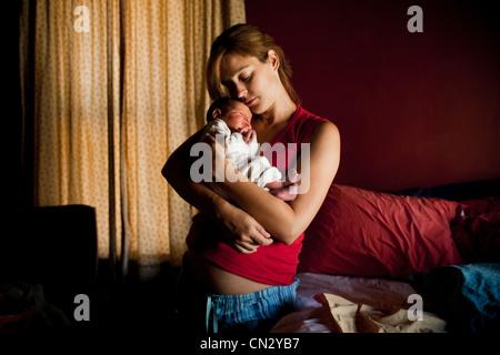 Madre abbracciando neonato figlio Foto Stock