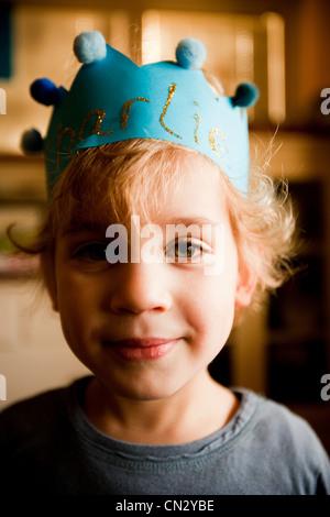 Ragazzo che indossa la corona di carta Foto Stock