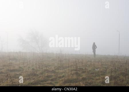 Ragazza adolescente in piedi in campo nella nebbia Foto Stock