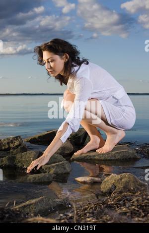 Donna in abito bianco accovacciato sulle rocce dal mare Foto Stock