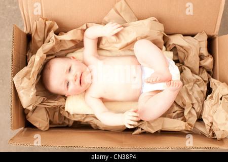 Bambina in una scatola di cartone Foto Stock