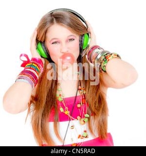 Young Teen girl ascoltando musica su cuffie e gomma di soffiatura Foto Stock