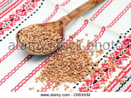 Il grano saraceno in cucchiaio di legno sul tessuto bianco Foto Stock