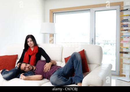 Coppia giovane in casa nel salotto seduta su un divano bianco Foto Stock