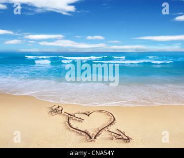 Cuore con freccia, come segno di amore, disegnata in riva alla spiaggia, con il vedere e sky in background.