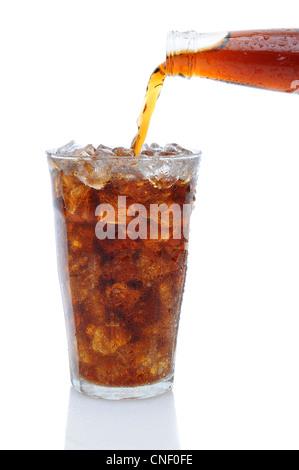 Una bottiglia di coca cola soda versando in un bicchiere riempito con cubetti di ghiaccio su uno sfondo bianco con la riflessione.
