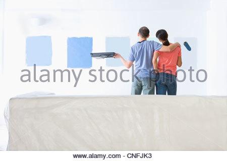 Giovane Azienda rullo di vernice e il vassoio ed esaminando la vernice blu campioni sul soggiorno parete Foto Stock