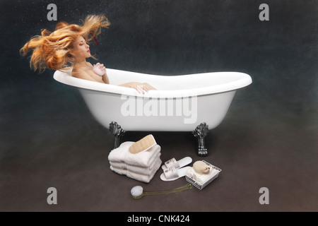 Giovane donna di balneazione subacquea se stessa nella sua Victoria + Albert clawfoot vasca da bagno