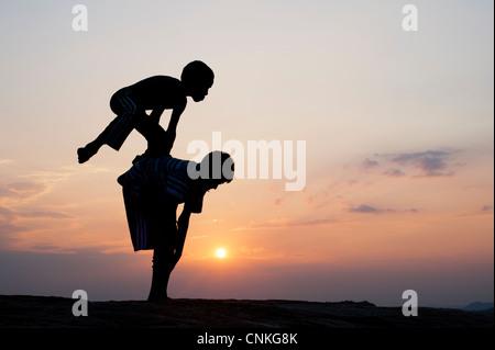 Silhouette di giovani indiani ragazzi giocare leap frog contro al tramonto. India Foto Stock