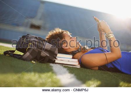 Lo studente ascolta mp3 player in erba Foto Stock