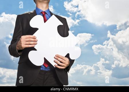 Imprenditore tenendo pezzo di puzzle Foto Stock