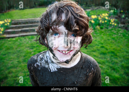 Ragazzo del volto sorridente coperto di fango Foto Stock