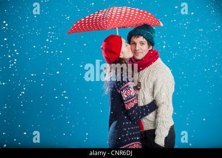 Coppia sorridente baciare in neve Foto Stock