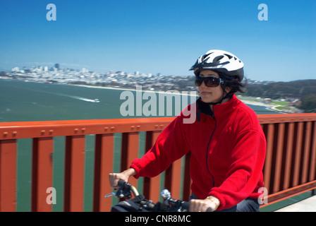Equitazione donna bici sul ponte urbano Foto Stock