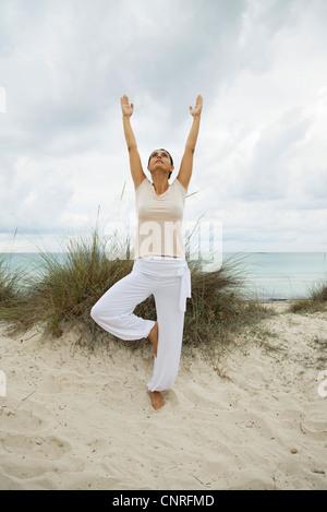 Donna matura in albero pongono sulla spiaggia, ritratto Foto Stock