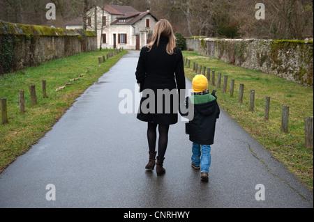 Madre e figlio camminando sul percorso nel villaggio, tenendo le mani, vista posteriore Foto Stock