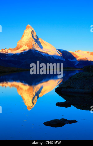Vista da un lago di montagna al Matterhorn nella luce dorata, Svizzera Vallese Foto Stock