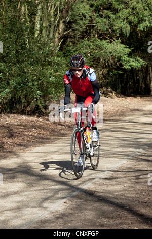 Un ciclista in competizione in una gara su strada sul vecchio Portsmouth Road, una strada appartata e tranquilla Foto Stock