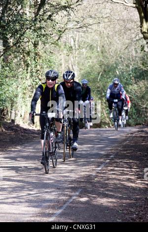 I ciclisti in competizione in una gara su strada sul vecchio Portsmouth Road, una strada appartata e tranquilla Foto Stock