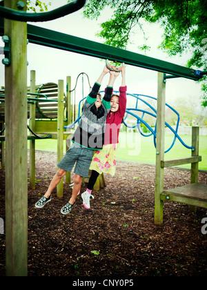 Un ragazzo e una ragazza swing insieme sul telaio di arrampicata. Foto Stock