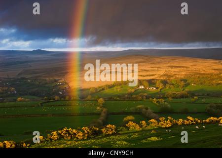 Rainbow al di sopra di terreni agricoli di rotolamento sui bordi del Parco Nazionale di Dartmoor, Devon, Inghilterra. Foto Stock
