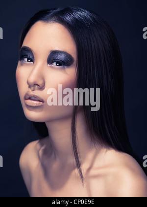 Bellezza artistica ritratto di una donna asiatica con spumante eyeshadows nero isolato su sfondo scuro Foto Stock