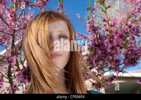 Molla, ragazza sorridente in telecamera con fiori di ciliegio e blu del cielo. Foto Stock
