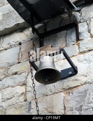 Si tratta di una foto di una grande campana impiccati contro la parete in una scuola o in una parete di pietra. Foto Stock