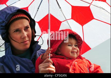 La madre e il neonato sotto un ombrello guardando la caduta di pioggia in una giornata invernale . Foto Stock