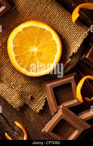 Fetta di arancia con quadrati di cioccolato sulla iuta e legno Foto Stock