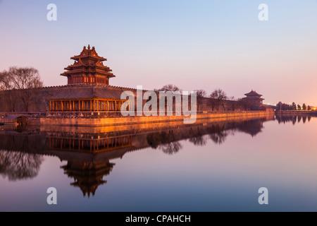 La parete e il fossato della Città Proibita di Pechino, Cina, guardando verso la porta nord dopo il tramonto. Foto Stock
