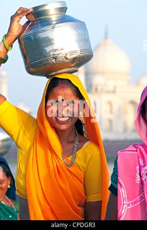 Donna che trasportano l'acqua vaso sul suo capo di fronte al Taj Mahal, Agra, nello stato di Uttar Pradesh, India, Foto Stock