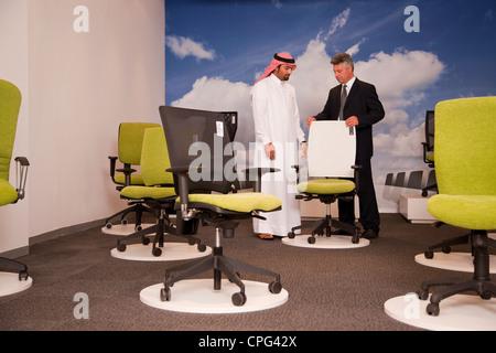 Venditore aiutare uomo arabo carrello per sedie da ufficio in negozio mobili. Foto Stock