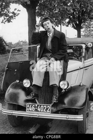 Donne, persone e degli anni cinquanta, la giovane donna in abbigliamento uomo si siede sul cofano del motore di Foto Stock