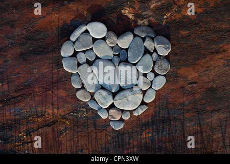 Forma di cuore i ciottoli su una texture di sfondo di ardesia Foto Stock