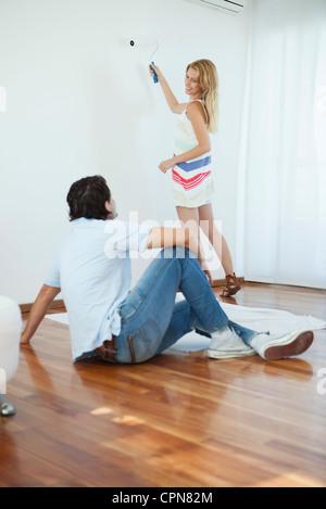 L'uomo guarda la donna dipinto sulla parete tramite il rullo di vernice Foto Stock
