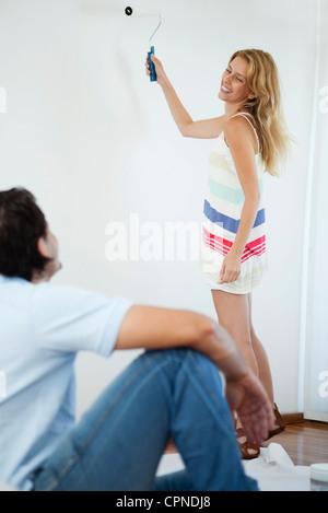 Giovane donna guardando il marito mentre la pittura parete con rullo di vernice Foto Stock