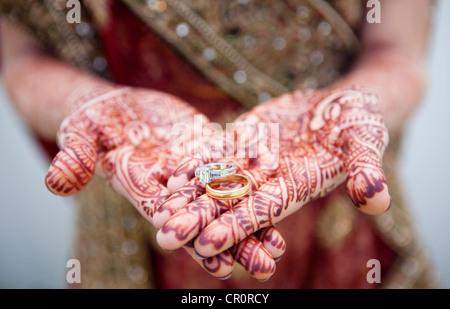 La donna caucasica con Indian Henna Tattoos sulle sue mani tenendo gli anelli di nozze Foto Stock