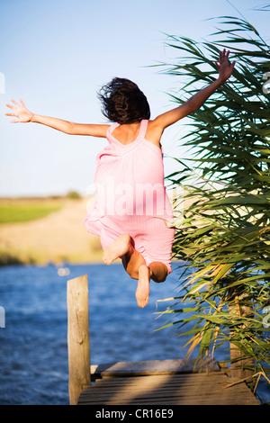 Donna salta fuori da dock nel lago Foto Stock