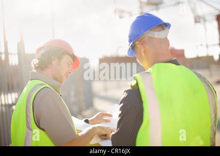 Lavoratori edili parlando sul sito Foto Stock