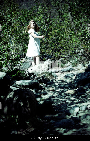Ragazza in un abito bianco correre a piedi nudi attraverso una foresta Foto Stock