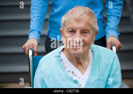 Senior donna in carrozzella con assistente dietro di lei.