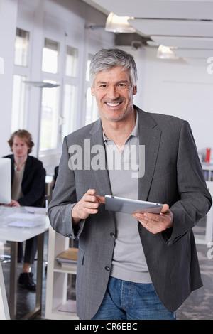 In Germania, in Baviera, Monaco di Baviera, uomo maturo con tavoletta digitale, collega di lavoro in background Foto Stock