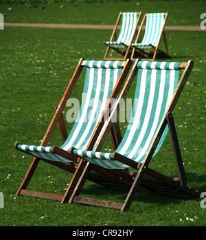 Quattro sedie a sdraio sul prato con margherite in St James Park, Londra Foto Stock