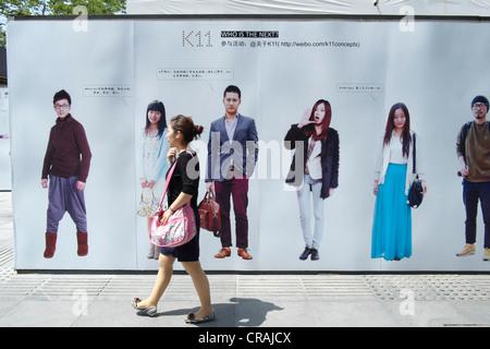 Giovani donne cinesi a piedi passato per la pubblicità tramite Affissioni Weibo sito di microblogging in Cina Shanghai Foto Stock