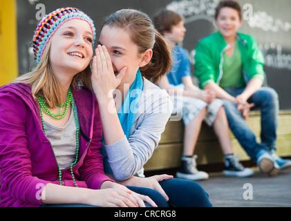 Due ragazze adolescenti whispering con due ragazzi in background Foto Stock