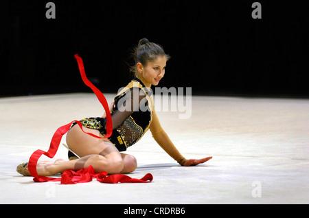 Donna facendo ginnastica ritmica con nastro Foto Stock