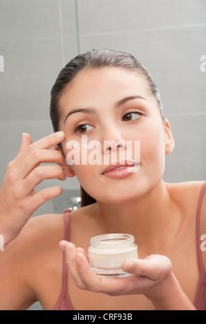 Donna di applicare una crema idratante viso a Foto Stock