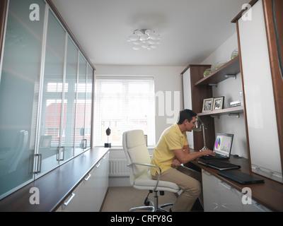 Uomo al lavoro su laptop in home office