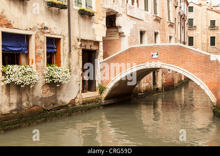 Un attraente ponte su un piccolo canale a Venezia, Italia Foto Stock